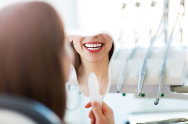 A patient at Ranches Family Dental looking at her smile in a mirror after a restorative appointment